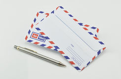 Stack of air mail envelopes with pen on white Stock Photo
