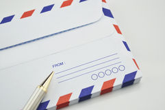 Stack of air mail envelopes with pen on white Stock Photos