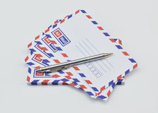 Stack of air mail envelopes and pen on white Royalty Free Stock Photos