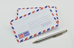 Stack of air mail envelopes and pen on white Stock Image