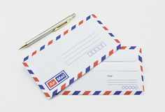 Stack of air mail envelopes and pen on white Royalty Free Stock Photography