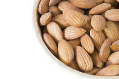 Stack of almonds in wooden bowl on white background isolated. Royalty Free Stock Photos