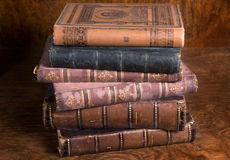 Stack of antique books. On aged wooden background taken from archive Stock Photography