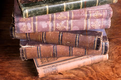 Stack of antique books backs. On aged wooden background taken from archive royalty free stock photography