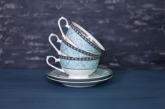 Stack of antique tea cups, isolated on white. Beautiful porcelain royalty free stock photos
