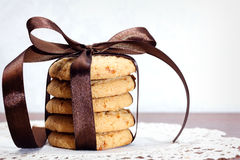 Stack of apple chip cookies taped with silk ribbon. Close up of stacked apple chip cookies taped with silk ribbon on white rustic napkin Stock Images