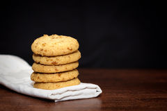 Stack of apple chip cookies on white napkin. Close up of stacked apple chip cookies on white napkin with wooden background Stock Photo