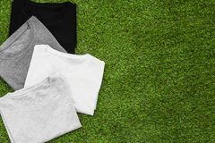 Stack of arranged different coloured mens T-shirt on grass background. Horizontal view stock image