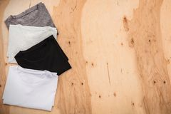 Stack of arranged different coloured mens T-shirt on wooden background. Horizontal view royalty free stock image