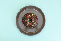 Stack of assorted donuts on black and blue cement background. Blue glazed doughnut with sprinkles on foreground. Copy space. Stack of assorted donuts on black royalty free stock photos