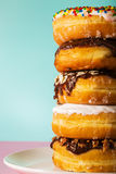 Stack of assorted donuts on pastel blue and pink background Stock Images
