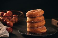 Stack of assorted donuts on a plate with milk on black background.  stock photo