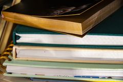 Stack of assorted hardback and paperback books or journals - some with bookmarks - closeup detail with selective focus. A Stack of assorted hardback and royalty free stock image