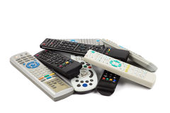 Stack of audio video remote control device in white background Royalty Free Stock Photos