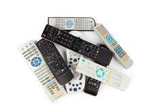 Stack of audio video remote control device in white background Royalty Free Stock Images