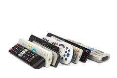 Stack of audio video remote control device in white background Royalty Free Stock Photo