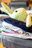 Stack of baby clothes with rabbit doll Stock Photos