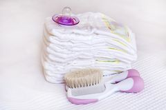 Stack of baby diapers. With hairbrush and pacifier Stock Image