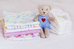 Stack of baby diapers and teddy bear. Stack of baby diapers with plush toy teddy bear royalty free stock photo