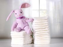 Stack of baby diapers on table with funny bunny. Bright background. stock photo
