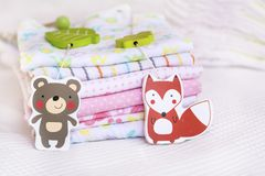 Stack of baby diapers. With wooden hanging toys Royalty Free Stock Photo