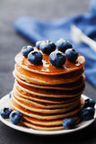 Stack of baked american pancakes or fritters with blueberries and honey syrup on rustic dark table. Delicious breakfast. Royalty Free Stock Images