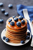 Stack of baked american pancakes or fritters with blueberries and honey syrup on vintage black table. Delicious dessert. Royalty Free Stock Photography