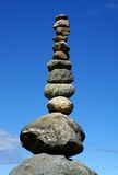 Stack of balanced pebbles, stones against blue sky Stock Photos