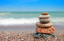 Stack of balanced stones on the beach. Zen stone little pile on beach over blue sky and sea royalty free stock photos