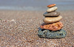 Stack of balanced stones on the beach. Zen stone little pile on beach over blue sea stock image