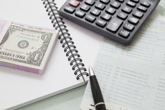 Stack of bank note and pen calculator on note book Royalty Free Stock Photo