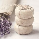 Stack of bars natural lavender soap. Bouquet of lavender in old newspaper. Scin care. Spa, relax, wellness time. Gift wrapping. stock photos