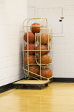Stack of basketballs in wire holder in gym corner Royalty Free Stock Image