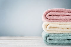 Stack of bath towels. On light wooden background closeup Stock Photos