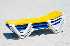 A stack of beach chairs in the sand. A stack of yellow and blue beach chairs in the sand Royalty Free Stock Image