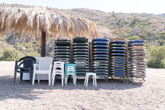 Stack of beach chairs under thatched umbrella Royalty Free Stock Image
