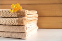 Stack of beige towels on wooden background. stock photo
