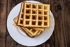 Stack of belgian waffles on a white plate wooden background Royalty Free Stock Photo