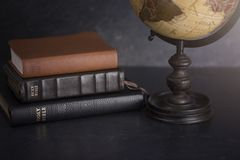 Stack of Bibles and a Globe on a Dark Background. A Stack of Bibles and a Globe on a Dark Background stock photos