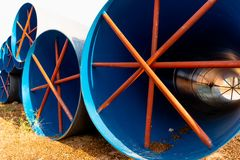 Stack of big blue water pipes used as water tunnel in irrigation project. 3 royalty free stock image