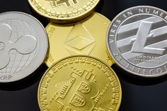 Stack of Bitcoins, Ethereum, Litecoin, Ripple and other crypto currencies on a table. royalty free stock photography