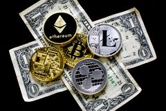 Stack of Bitcoins, Ethereum, Litecoin, Ripple and other crypto currencies on top of dollar bills on a black table.. stock photo
