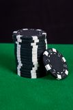 Stack of black chips on a green playing table Royalty Free Stock Photography