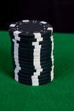 Stack of black chips on a green playing table Royalty Free Stock Image