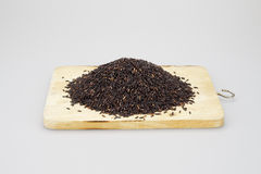 Stack of black rice put on a wooden chopping block Royalty Free Stock Image
