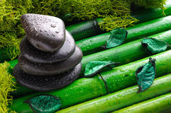 Stack of black stones for massage on bamboo top view Royalty Free Stock Images