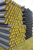 Stack of black yellow corrugated plastic pipes.  Stock Photography