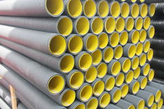 Stack of black yellow corrugated plastic pipes.  Stock Images