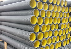Stack of black yellow corrugated plastic pipes.  Stock Image