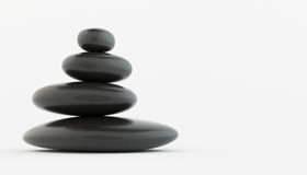 Stack of black zen stones on white floor. Stock Images